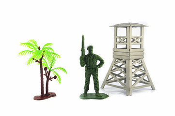 Toy soldier isolated on white background / Green miniature toy soldier watchtower and palm tree