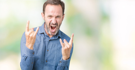 Handsome middle age elegant senior man over isolated background shouting with crazy expression doing rock symbol with hands up. Music star. Heavy concept.