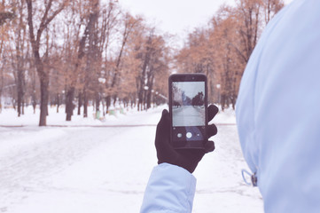 girl taking pictures of a winter alley on a smartphone