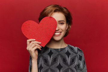 Beauty cheerful Young fashion model Girl with big Valentine Heart in hands. Love. Beautiful young woman in dress. Valentines Day symbol. Red background. - Image