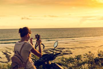 Young woman taking photo of sunset on motorbike. Bali island. Indonesia.