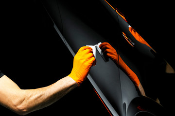 Car polish wax worker hands polishing car. Buffing and polishing vehicle with ceramic. Car detailing. Man holds a polisher in the hand and polishes the car with nano ceramic. Tools for polishing