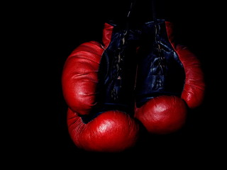 Old leather red boxing gloves hanging in the dark