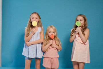 three girlfriends sisters eat sweet lollipop with sweet chocolate dessert