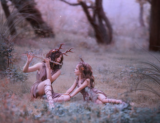 creative fabulous family shooting, faun mom plays lullaby on flute for her child, fairytale characters deer in long brown dresses are relaxing in clearing, art photo for mother's day, parents care