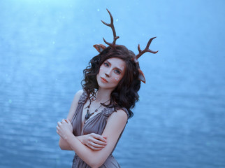 girl in the image of a faun, costume and make-up of a deer, a fantastic character of the spirit of forest in brown dress, portrait photo of a sad lady on background of magical lake, blue cool shades