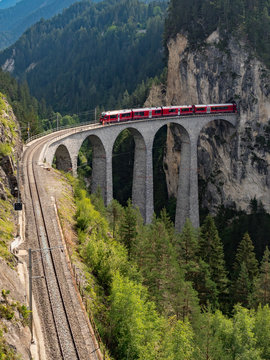 Red train on famous Landwasser Viaduct bridge.The Rhaetian Railway section from the Albula/Bernina area (the part from Thusis to Tirano, including St Moritz), Switzerland, Europe. August, 2018