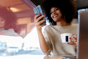 Portrait of attractive afro woman using mobile phone at the coffee shop