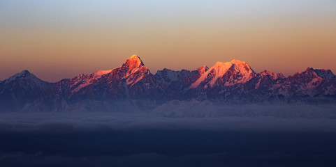 Mountain Range Sunrise, mountains glowing in the sunshine at dawn. Snow covered mountain peaks in the distance, panoramic view. Purple, Orange atmosphere. Sichuan Province China. Rugged wilderness