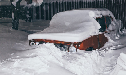 Snow storm in the night city. Huge drifts and stuck cars