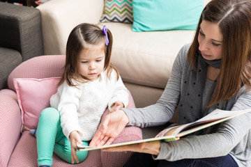 Toddler And Mom Going Through Picture Book