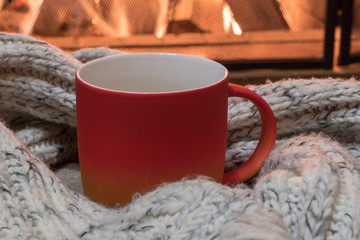Cozy scene before fireplace and red mug with tea, and wool scarf.