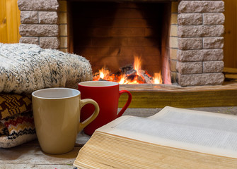 Cozy scene before fireplace with two big mugs with tea, opened book and wool scarf.