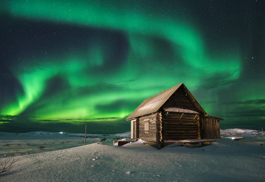 Landscape with northern lights over a wooden house on the coast of the Barents Sea on the Kola Peninsula at night at high ISO sensitivity
