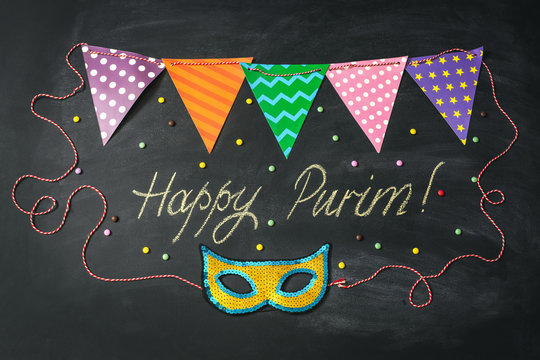 Carnival mask made of gold glitter, sparkles and inscription Happy Purim on chalkboard