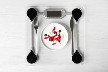 Scales with weight loss pills and cutlery on wooden background, top view