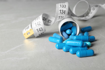 Weight loss pills, bottle and measuring tape on table