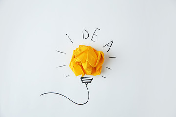 Composition with crumpled paper as lamp bulb and word IDEA on white background Wall mural