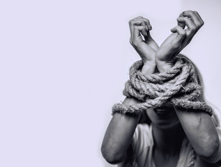 Concept of gender discrimination against women.  Hands tied up with rope of woman. Black and white portrait photo.