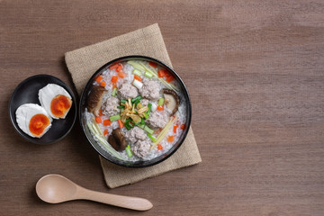 top view of boiled rice clear soup with pork in a ceramic bowl on wooden table, served with salted duck egg. homemade style food concept.