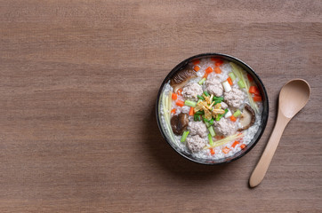 top view of boiled rice clear soup with pork in a ceramic bowl on wooden table. homemade style food concept.