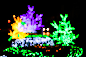 Beautiful bokeh light background, White and green bokeh light decorated in party, neon light shine on green bush of tree in the night, background for Christmas and new year celebration