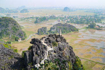 Hang Mua Mountain viewpoint or Mua Caves Ecolodge, Stunning view of Tam Coc area with mountain range, rice fields and waterway.