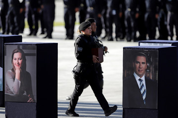 A policewoman carries an urn with ashes next to photographs of Martha Erika Alonso, a senior opposition figure and governor of the state of Puebla and her husband SenatorRafael Moreno during a homage in Puebla