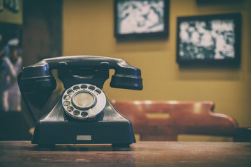 old style telephone on working desk with blurred background of photo hanging on wall, vintage tone