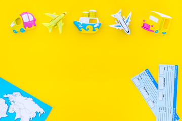 planning trip with child with map, tickets and toys yellow background top view space for text. Time to travel.