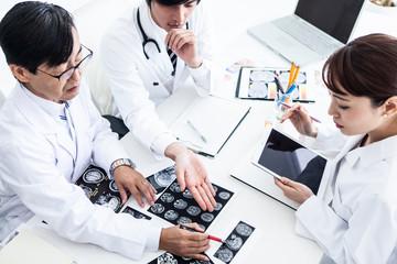 レントゲン写真を見ながら話し合いを進める医師三人