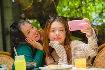young happy and cute Asian Chinese girlfriends taking selfie portrait picture with mobile phone camera for using on internet social media while having healthy brunch at cafe