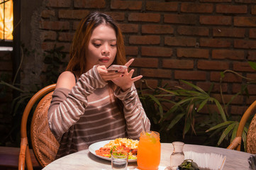 young pretty and happy Asian Korean student girl sitting at sweet coffee shop taking photo of her meal with mobile phone camera in internet social media food blogger concept