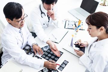 三人の医者がレントゲン写真をみながら話し合いを行っている風景
