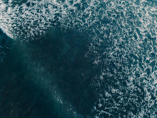 Aerial view beautiful of sea waves from drone. Stock image of blue color of ocean water, sea surface. Top view on turquoise waves, clear water surface texture.  Top view, amazing nature background