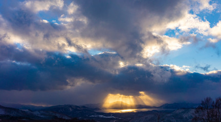 田沢湖 夕日 雲間から照らす光 冬