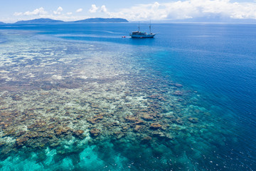 Foto op Plexiglas Asia land Aerial of Beautiful Coral Reef and Traditional Ship in Raja Ampat