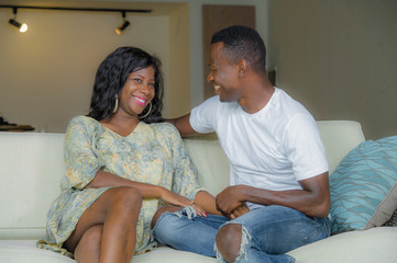 young attractive and happy black African American couple relaxed at home sofa couch talking sweet enjoying together and smiling in man and woman in love enjoying