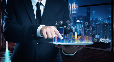 Businessman working on digital table with intelligence iot and smart city showing on virtual screen .