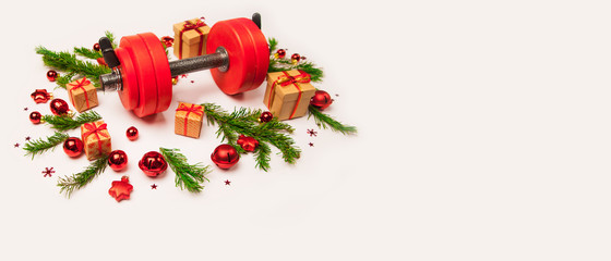 Christmas or New Year on a white background. Composition with dumbbells, gift, red and gold glass balls, fir tree branches for healthy lifestyle and sport