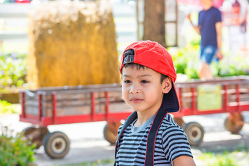 Portrait of Asian boy wearing a hat and smiled happily in park.