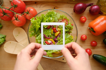 Hands holding photo frame from polaroid over wooden table with fresh vegetables.