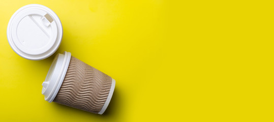 Cardboard cup of coffee on yellow background