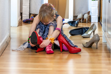 Little girl wearing big high-heeled mother's shoes