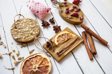 collection of handmade soap with dried flowers of rose, orange, oat, cinnamon sticks on a white wooden background
