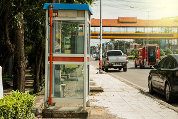 Old telephone booths that are on the side of the road