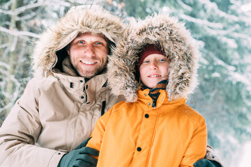 Father and son dressed in Warm Hooded Casual Parka Jacket Outerwear walking in snowy forest cheerful smiling faces portrait. Father and son relatives and winter outfit concept image.