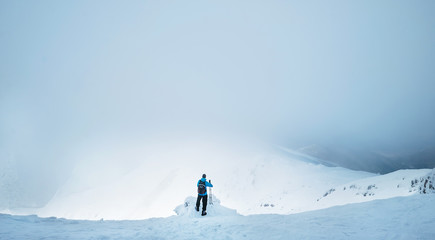Winter Trekker staying on mountain peak he climbed and enjojing wide panorame view of valley covered by storm clouds. Active winter trekking concept image.