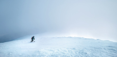 Fast going skier ride down the mountain hill into the storm clouds. Active winter sport concept image.