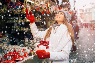 Smiling girl choosing decorations at Christmas market. Portrait of smiling young longhaired blond woman buying gifts at Christmas fair in evening. Enjoy winter holiday mood.